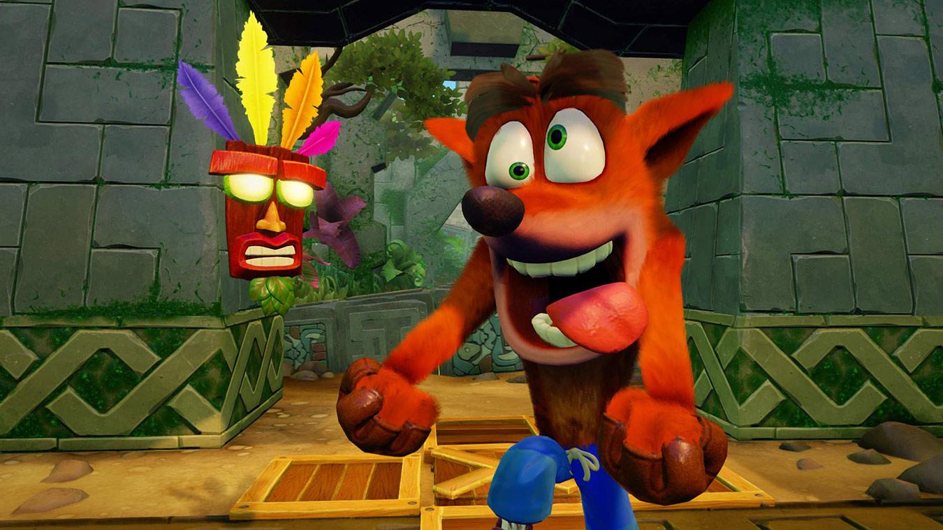Crash laver et fjollet ansigt ved siden af træmasken Aku Aku