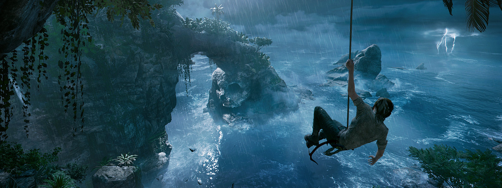 Lara Croft swings from a vine over water on a jungle island