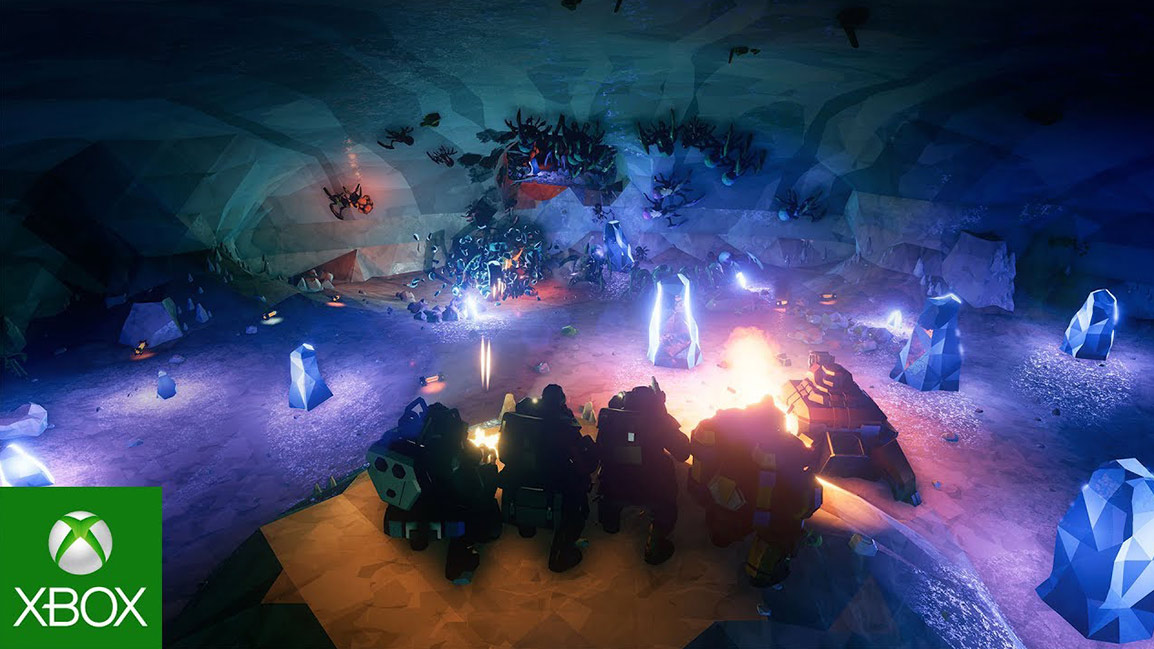 4 space dwarves stand on a rock in a cave and fire down at alien like enemies
