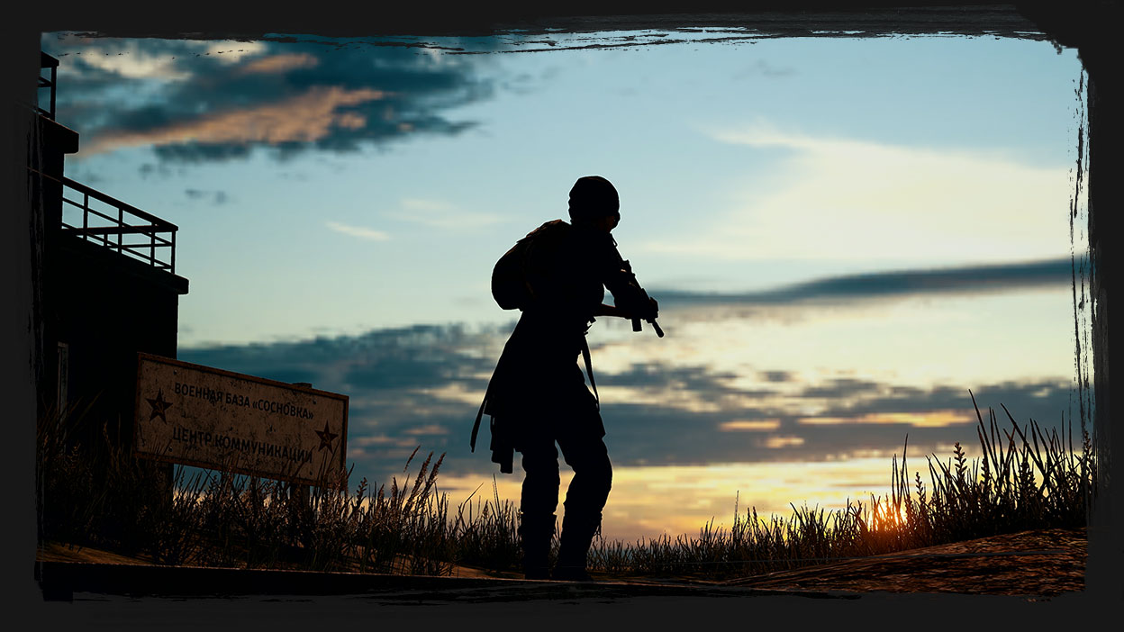 A character holds a gun with a sunset in the background.