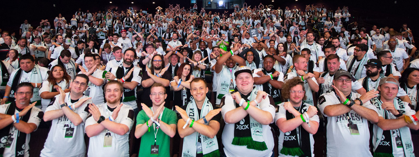 "A large gathering of people wearing Xbox FanFest shirts hold up their arms, making an ""X"" with their arms."