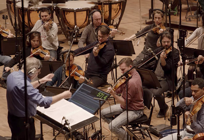 Conductor Allan Wilson conducts the string section of an orchestra during a recording session.