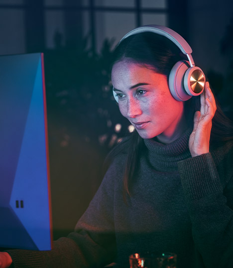 A women wearing the Bang and Olufsen headset while using the computer