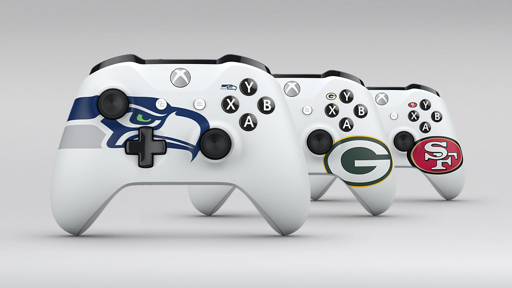 Three white Xbox controllers, each featuring an NFL team logo.