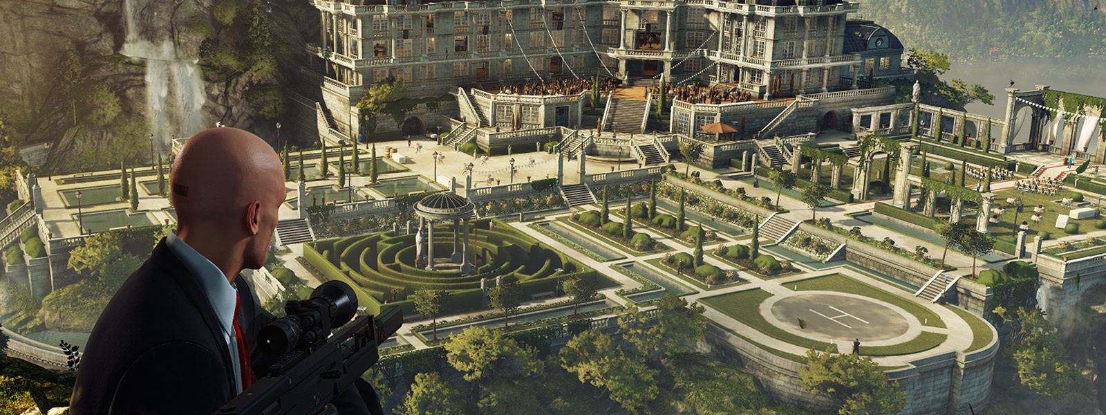 Agent 47 holds a sniper rifle while overlooking a large mansion on the side of a mountain