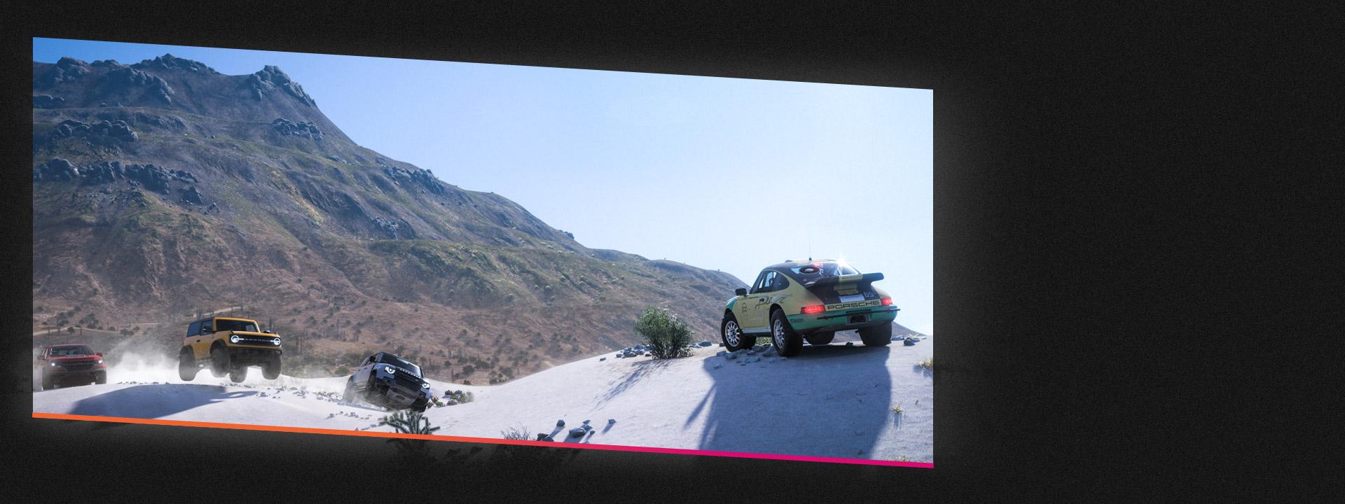 모래에서 오프로드 경주를 펼치는 자동차 네 대.