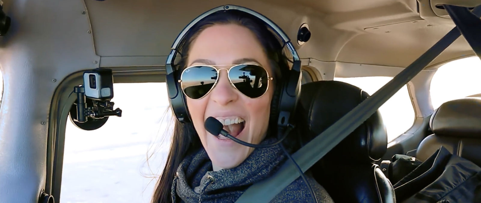 Pilot Emilie flying a plane with a headset and sunglasses