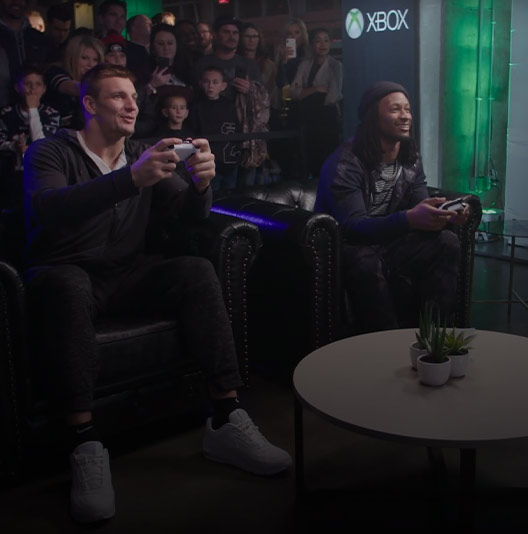 New England's Rob Gronkowski, Los Angeles' Todd Gurley, and host Phillip McClure play Madden NFL 19 in front of a studio audience