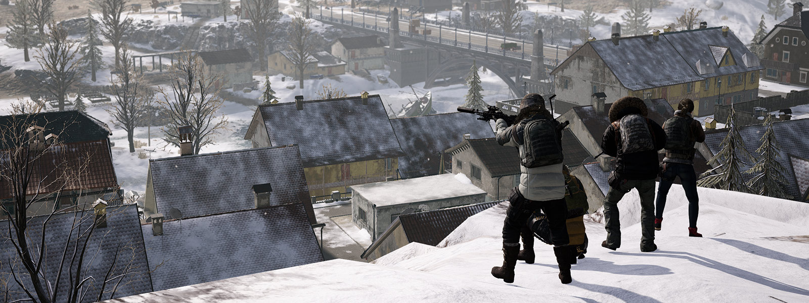 4 players stand on snow covered hill while looking down at a town full of houses
