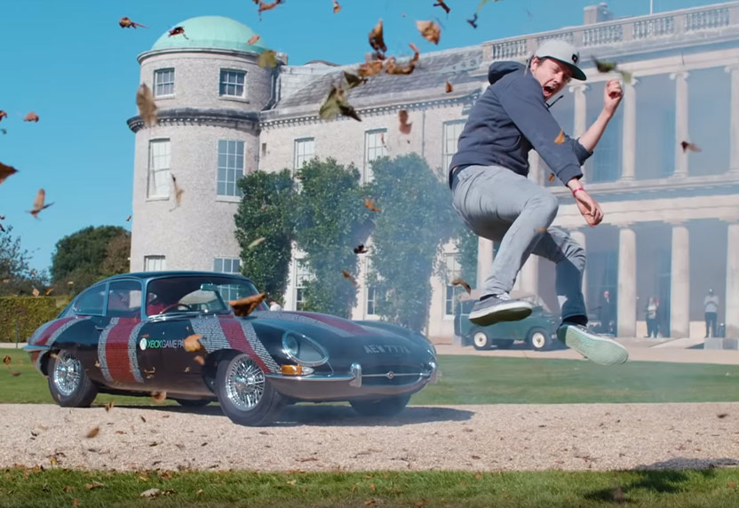 Man mid-jump in front of a parked Jaguar in the driveway of the Goodwood Estate