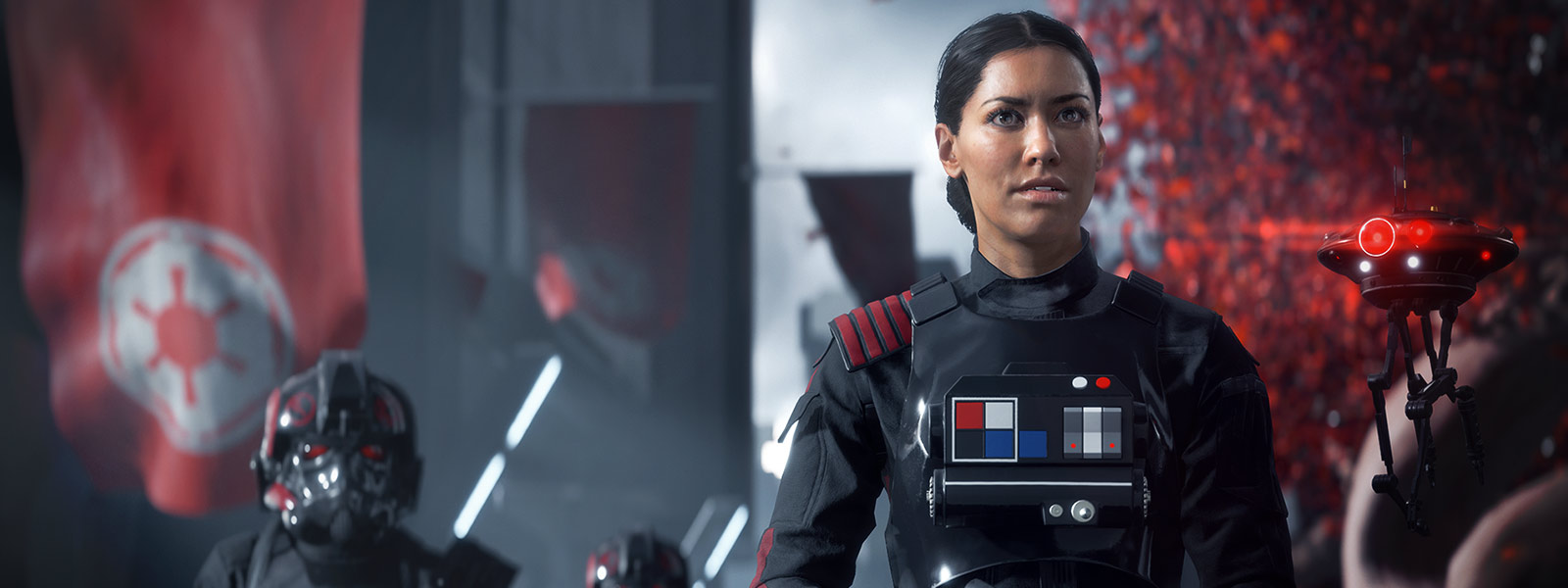 Front view of Iden Versio standing outside with her drone hovering next to her
