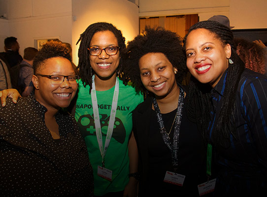 Four black women smiling for a group photo
