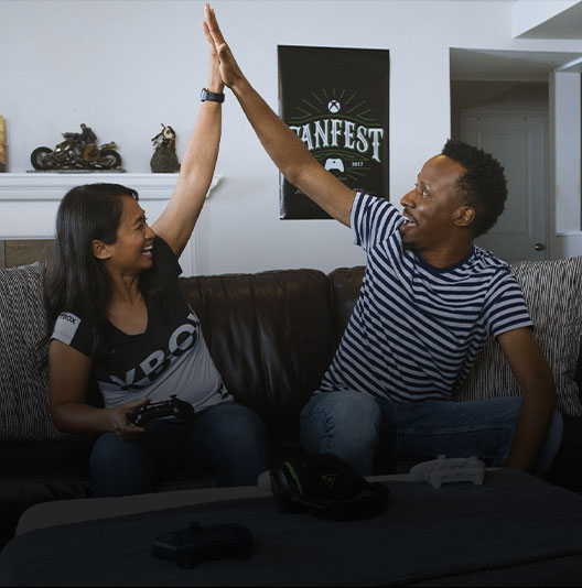 Two gamers share an enthusiastic high five while playing Xbox One.