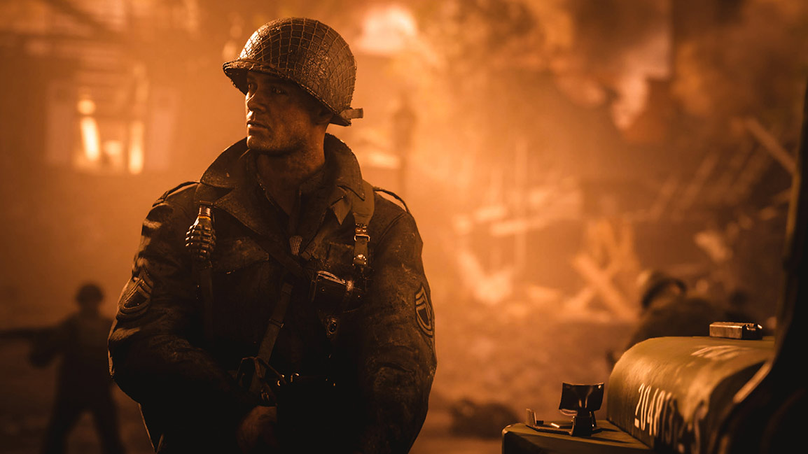 soldier looks off into distance with building on fire in the background