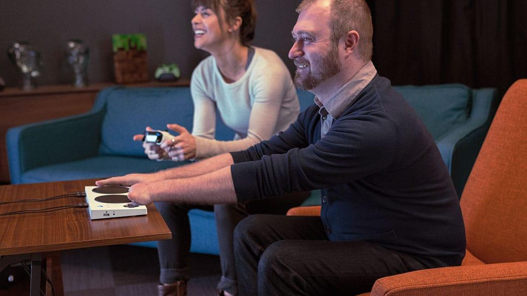 Eine Person spielt Xbox mit einem Xbox Adaptive Controller gegen einen anderen Spieler