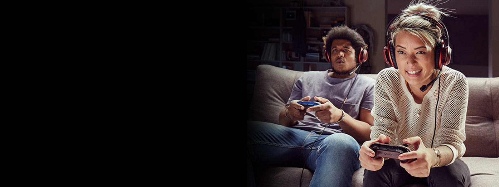 Two gamers sitting on a couch and playing Xbox together