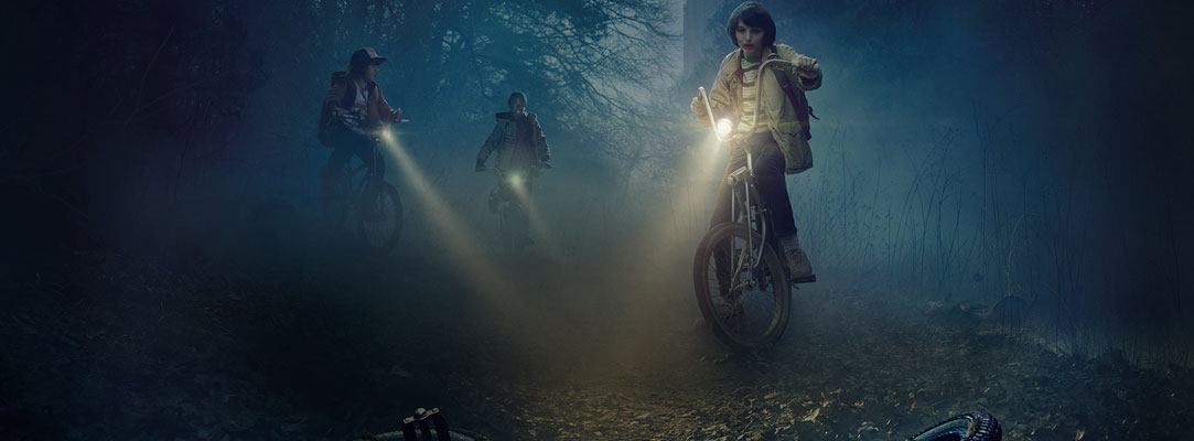 Stranger Things characters biking in the dark
