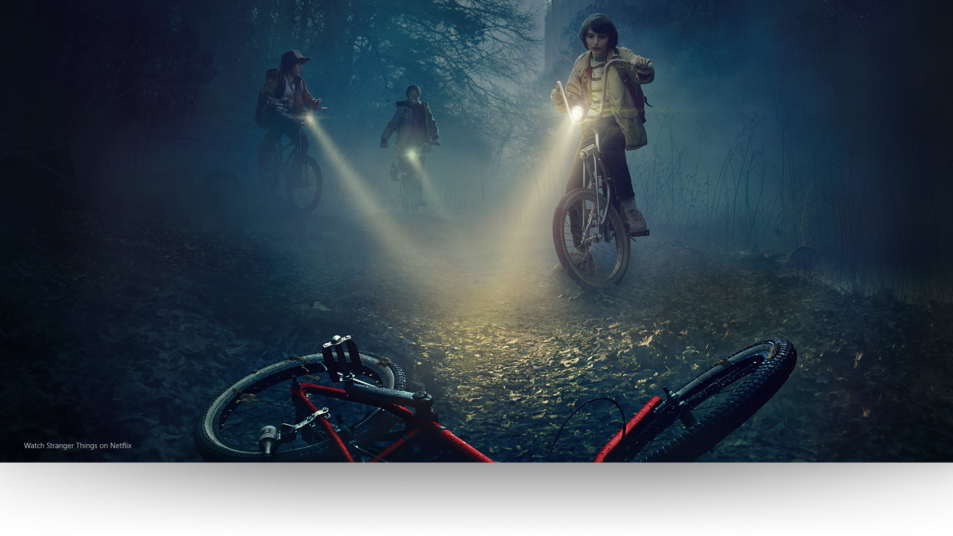 Stranger Things – Dustin, Lucas and Mike shine their lights on an abandoned bicycle on a gloomy forest path.