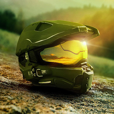 Master Chief's signature Spartan helmet rests on the ground reflecting sunlight in front of sweeping hills of evergreen trees.
