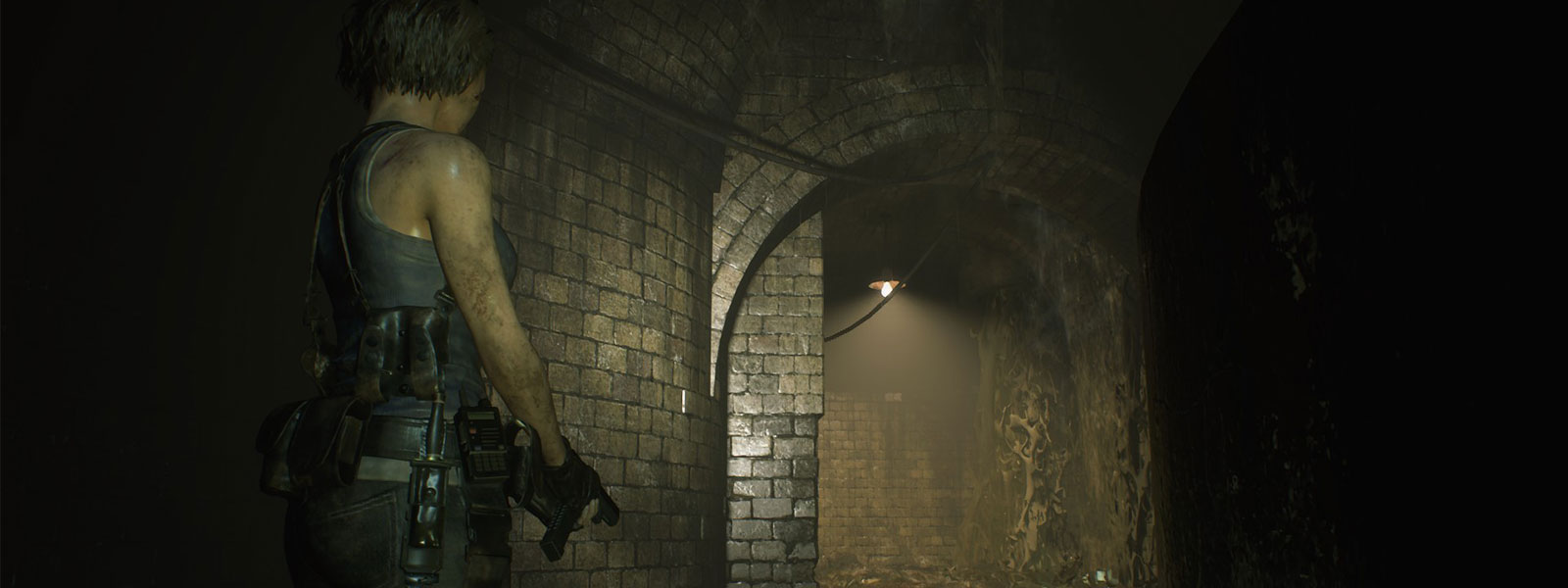 Jill Valentine stands in a dark tunnel with her gun drawn.