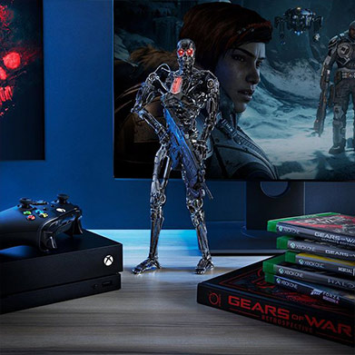 A figure of a T-800 endoskeleton holding a Lancer stands in front a TV playing Gears 5.