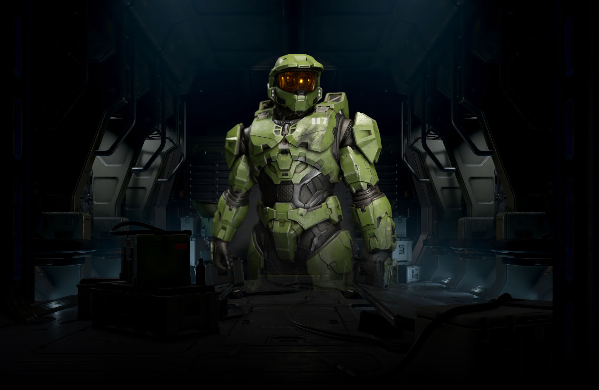 "Halo Infinite. Master Chief stands in a dimly lit room, the front of his armour slightly damaged under the ""117"" on his chest."