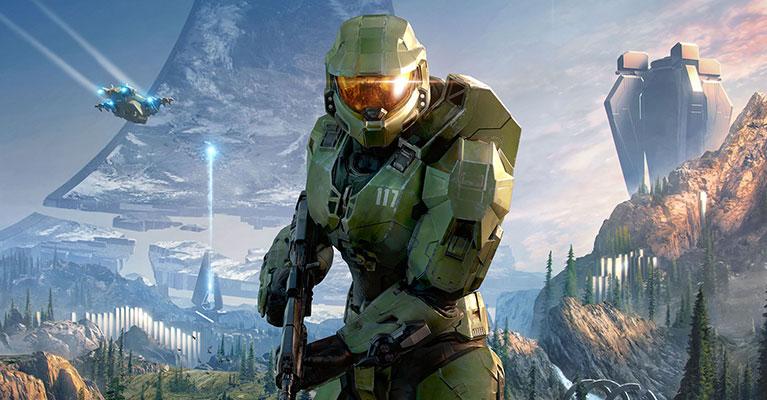 Master Chief som har sitt vapen redo med en Halo-ring i bakgrunden.