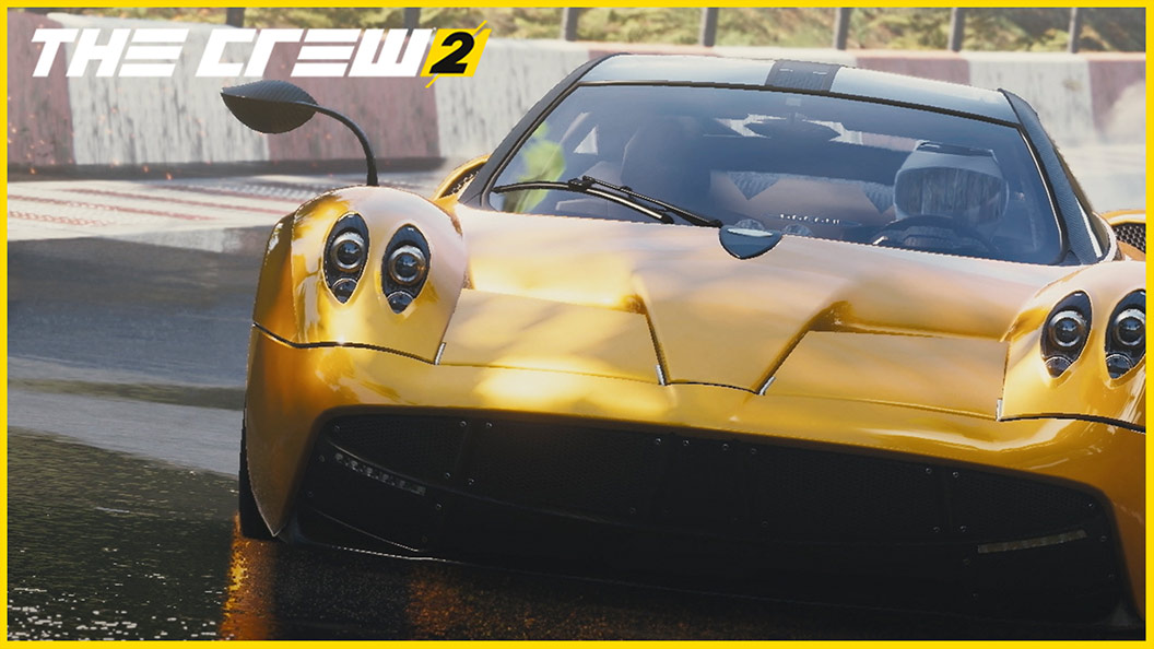 Front view of driver in gold race car on race track