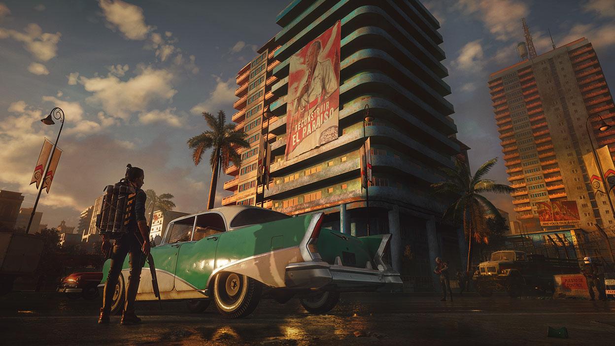 Ein Mann mit einer Waffe steht in Far Cry 6 neben einem Oldtimer mit hoch aufragenden Gebäuden im Hintergrund.