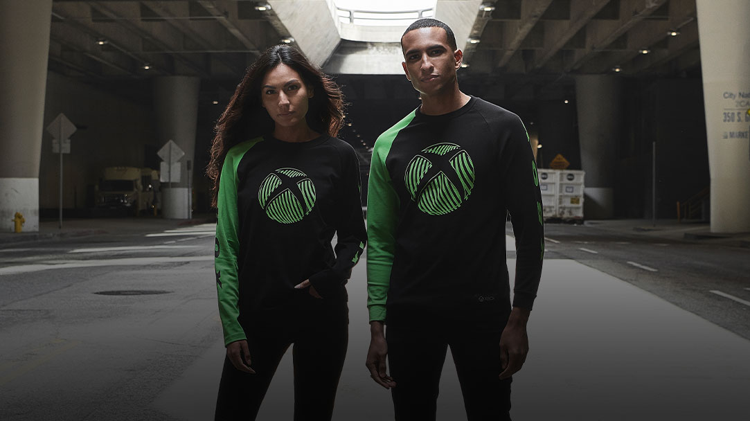 A man and a woman wearing Xbox Official Gear Wave Sphere long sleeve tee
