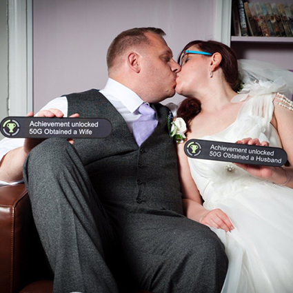 A married gaming couple sitting on a couch next to an image of toppers on their wedding cake, submitted by TooStupidtoCare