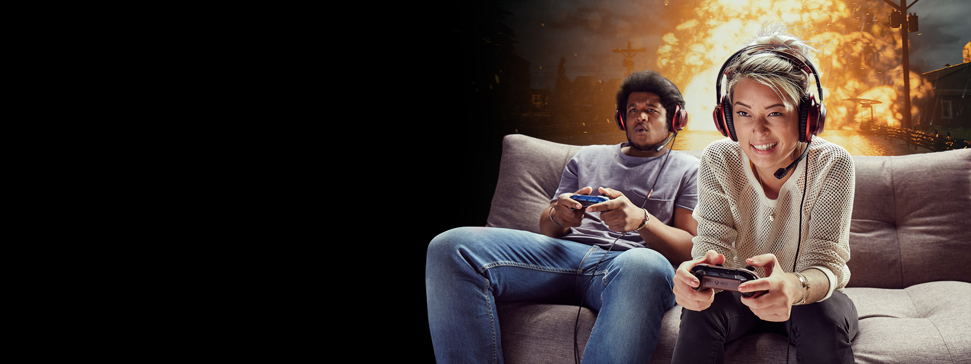 Two gamers sitting on a couch, immersed in an explosive Xbox One game