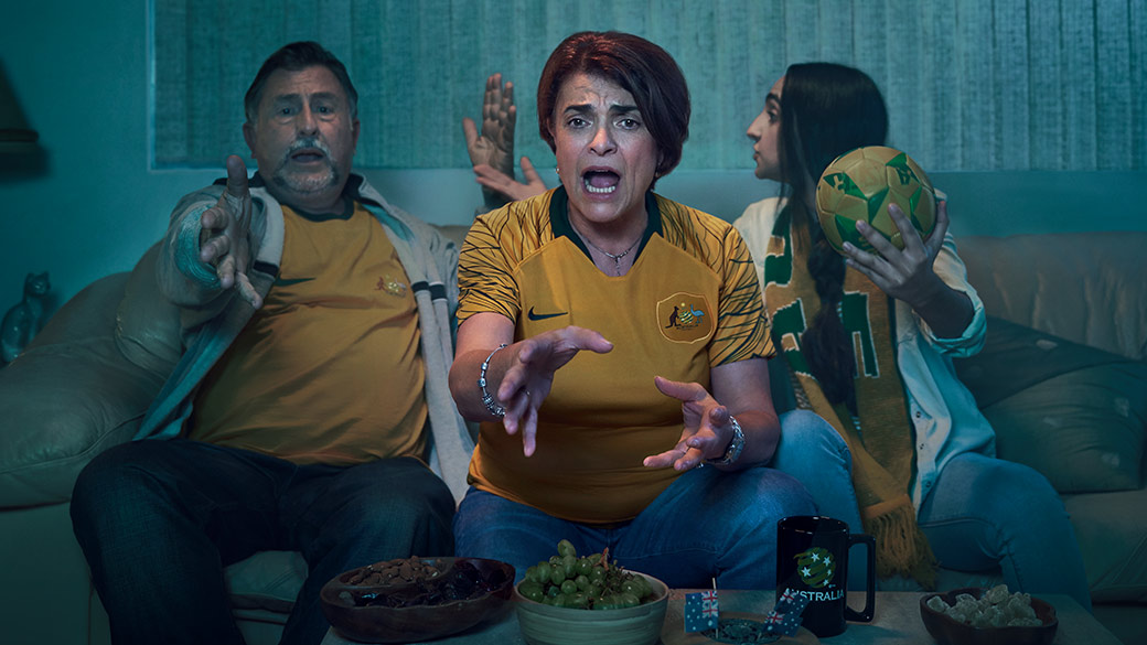 Family of three watching football wearing Australian football jerseys