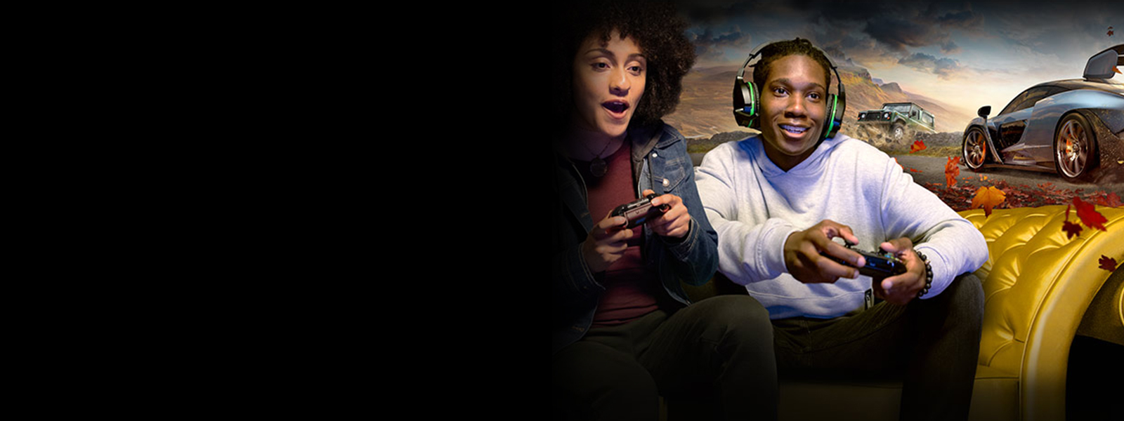 Two gamers sitting on a gold couch, playing Xbox together in front of a Forza Horizon 4 visual