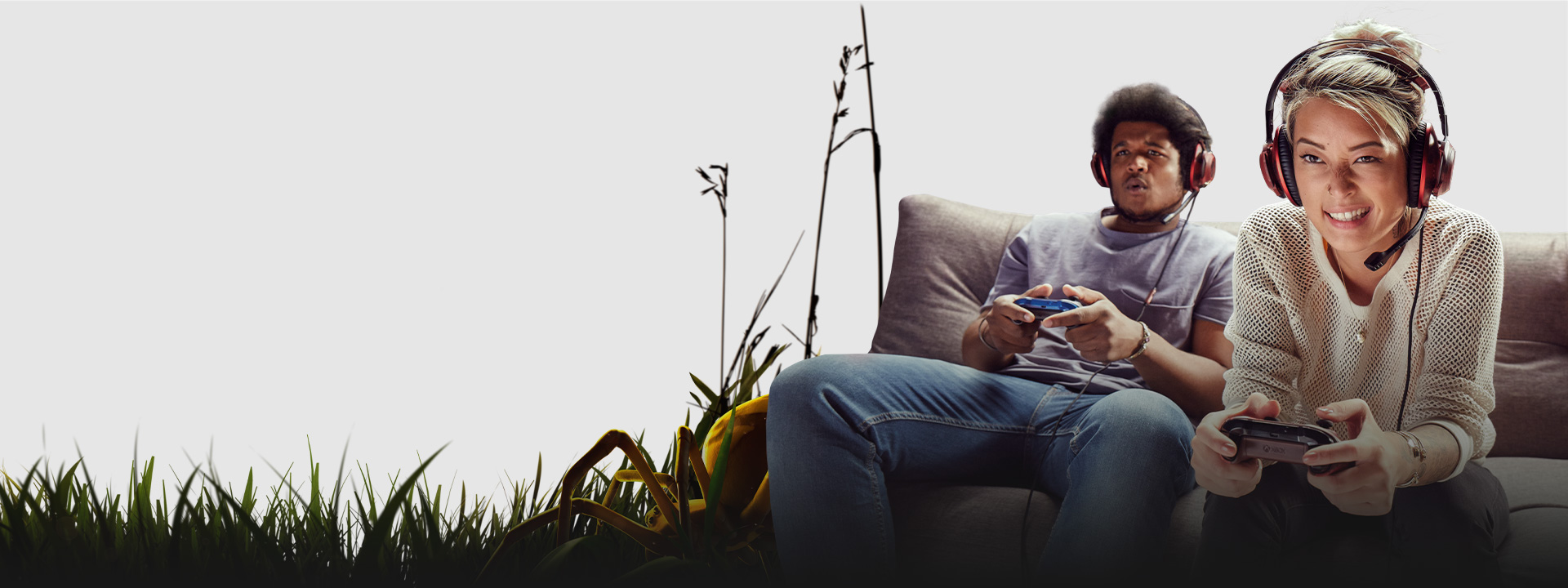 Two gamers sitting on a sofa in a grassy scene from Grounded