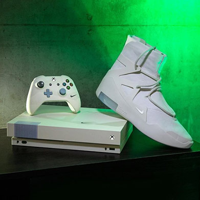 White Xbox console and controller next to a Nike Air Fear of God sneaker