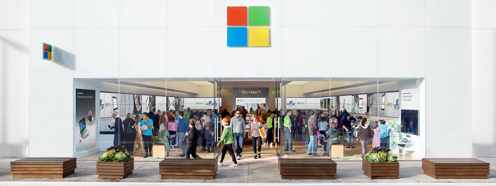 A view of the front of a Microsoft Store filled with shoppers