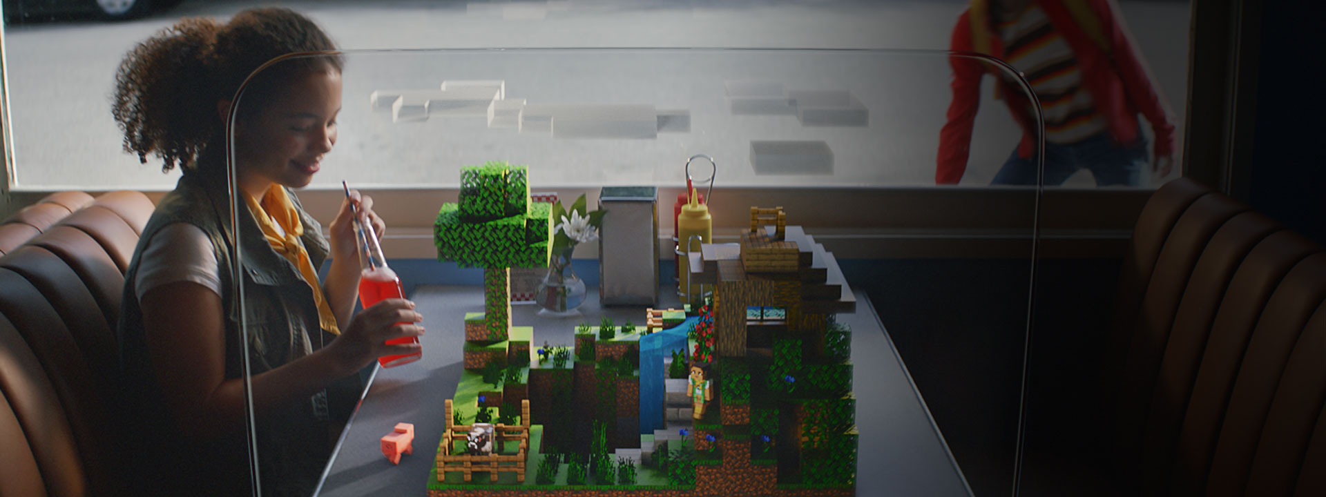 Girl sitting at a table with Minecraft scene on the table