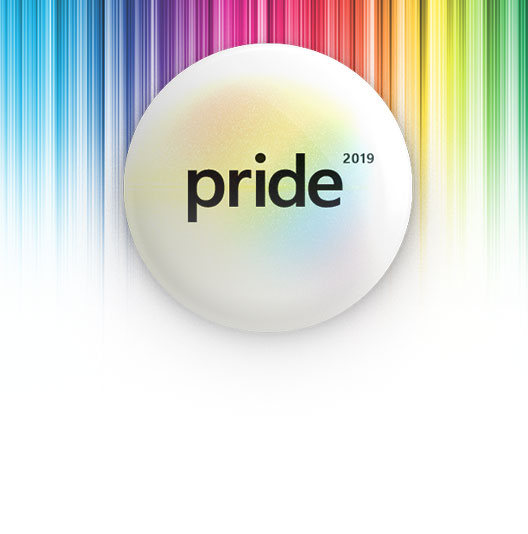 A white pin that reads Pride placed over a rainbow background