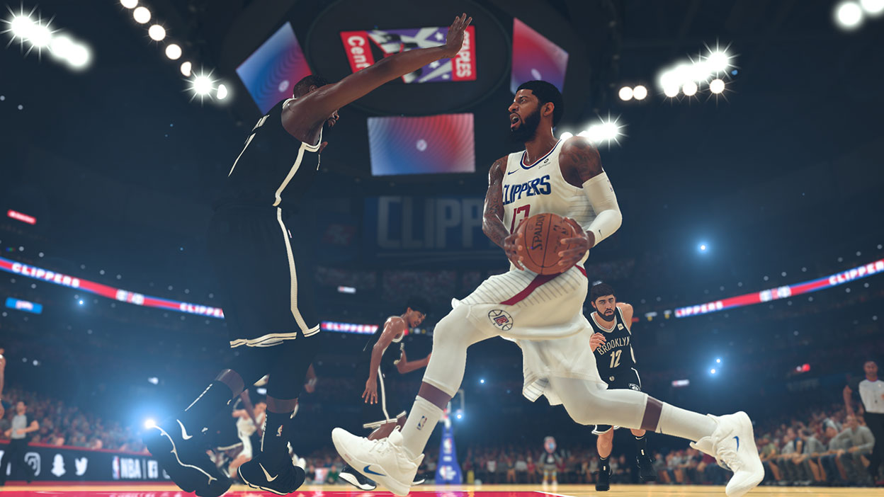 Clippers player with basketball going against a Brooklyn player.