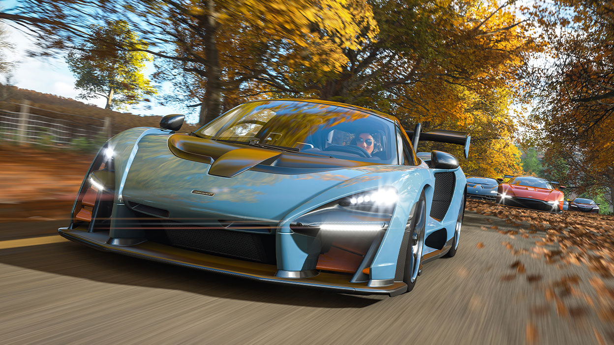 A McLaren Senna speeds down a tree-lined road