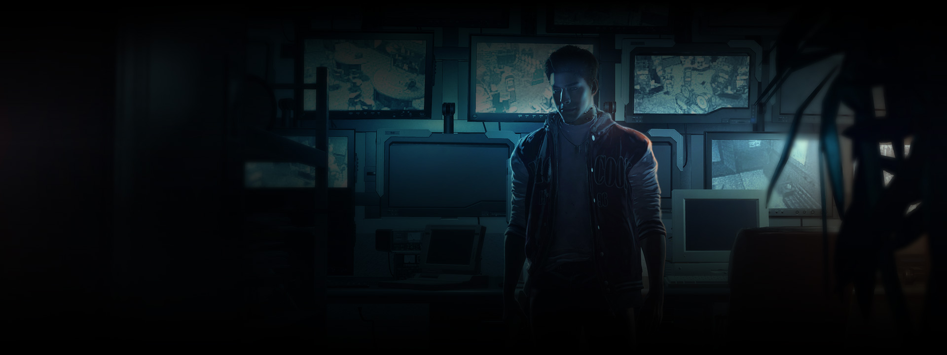 A young man stands in front of a wall of lit up monitors.