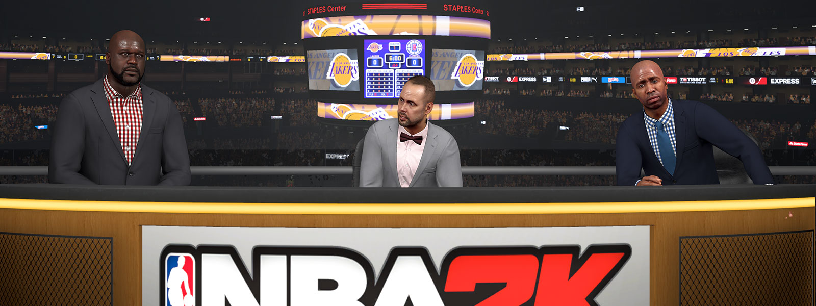 Shaq and another caster behind a NBA 2K analyst desk with the scoreboard behind them in a basketball arena