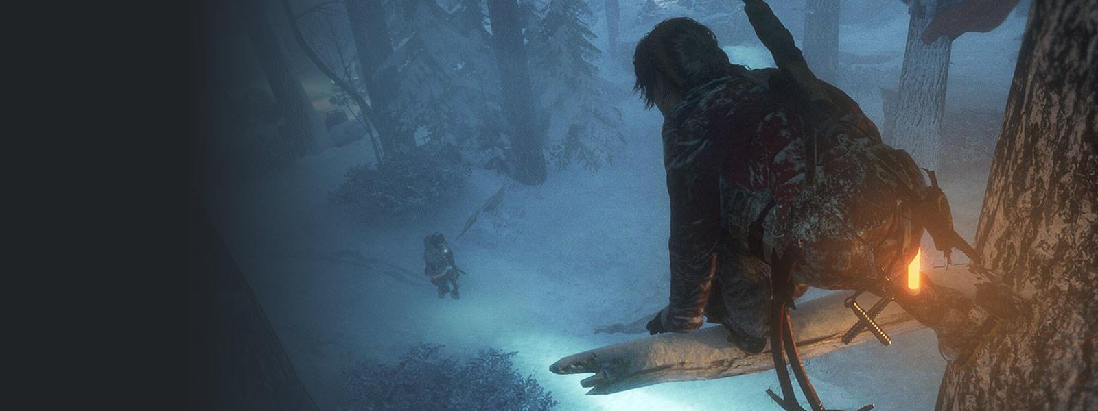 Lara num ramo de uma árvore coberta de neve, preparando-se para atacar um inimigo que passa por baixo