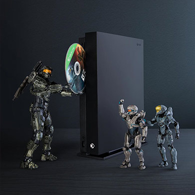 Halo figurines inserting a Halo game disc into an Xbox One