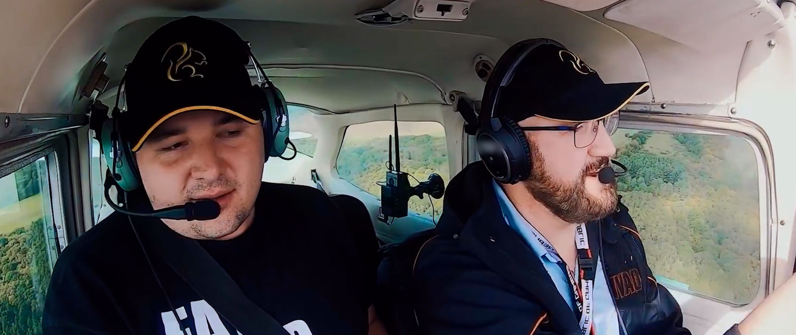 Two people with headsets and hats flying a plane