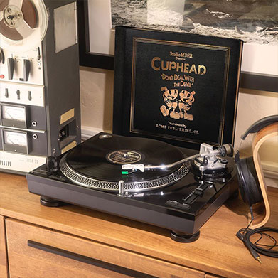 A turntable playing the Cuphead soundtrack among modern and classic audio equipment.