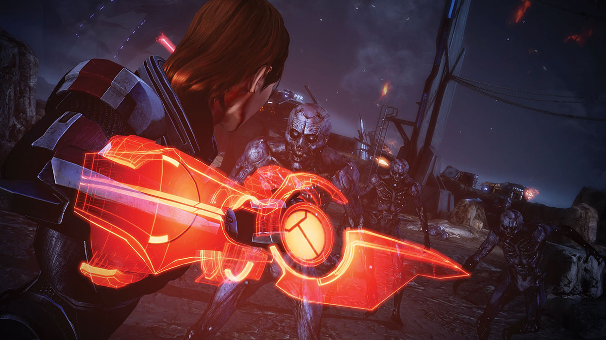 Female Shepard uses an Omni-blade to attack a group of undead enemies