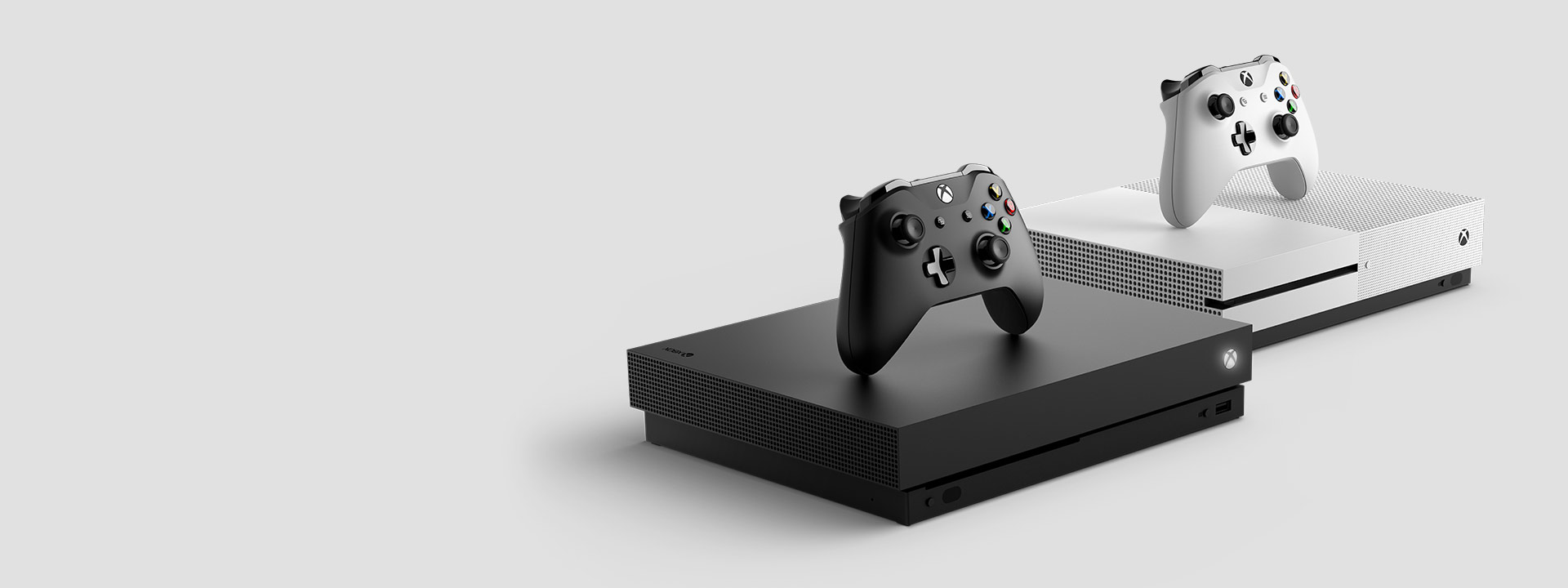 Side view of the Xbox One X and Xbox One S with Wireless Controllers on top