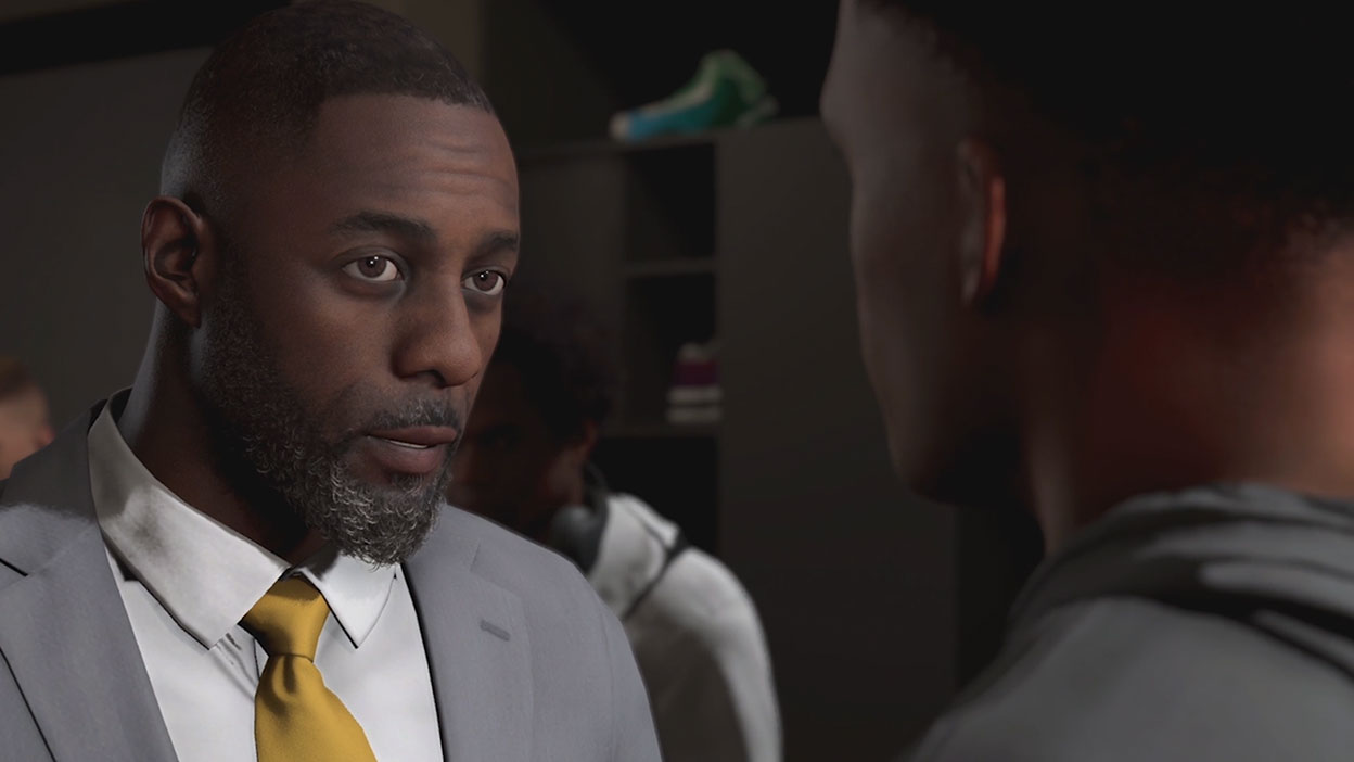 Idris Elba in a suit talking to a player.